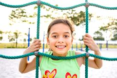 Young girl poking head through climbing rope Royalty Free Stock Photos
