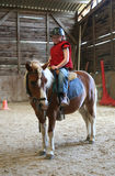 Young girl on pony. Female child mounted on small horse in indoor riding arena stock image