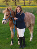 Young Girl With Pony. A young girl in riding clothes stands with her pony Stock Photos