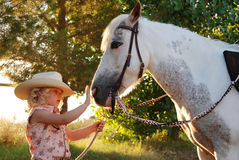 Young girl with pony. Cute young girl dressed in cowgirl clothes stroking her pet pony's nose Royalty Free Stock Photography