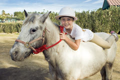 Young Girl on a Pony. Young girl lies atop her pet pony Royalty Free Stock Image