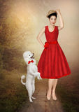 Young girl and poodle. Young girl in a red dress, in straw hat with a sly smile, looks at the white poodle standing on two legs Royalty Free Stock Image