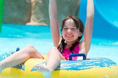 Young girl in the pool. A young girl riding a tube in the pool Stock Photo