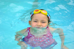 Young girl in the pool. Trying to swim Royalty Free Stock Image