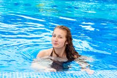 Young girl in pool. Blue, happy. The beautiful smiling young girl in pool Stock Image