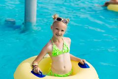 A young girl in the pool on an inflatable lap. The girl is swimming in the pool Royalty Free Stock Photos