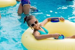 A young girl in the pool on an inflatable lap. The girl is swimming in the pool Royalty Free Stock Photo