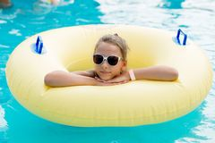 A young girl in the pool on an inflatable lap. The girl is swimming in the pool Stock Photography