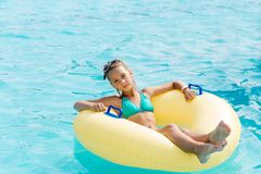 A young girl in the pool on an inflatable lap. The girl is swimming in the pool Royalty Free Stock Photography