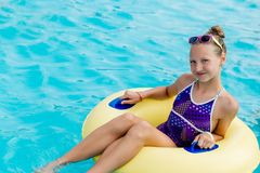 A young girl in the pool on an inflatable lap. The girl is swimming in the pool Stock Image