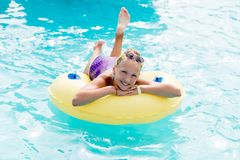 A young girl in the pool on an inflatable lap. The girl is swimming in the pool Stock Photos