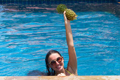 The young girl in the pool with pineapple in hands and a happy smile wearing sunglasses and a yellow bathing suit. The young girl in the pool with pineapple in Royalty Free Stock Images