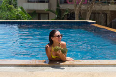 The young girl in the pool with pineapple in hands and a happy smile wearing sunglasses and a yellow bathing suit. The young girl in the pool with pineapple in Stock Photo