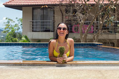 The young girl in the pool with pineapple in hands and a happy smile wearing sunglasses and a yellow bathing suit. The young girl in the pool with pineapple in Royalty Free Stock Photo