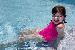 Young Girl In Pool with Pink Bathing Suit. Blue water. Swimming. Playing Stock Image