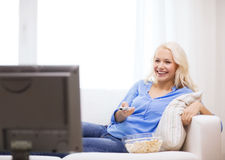 Young girl with popcorn watching movie at home. Food, happiness and people concept - smiling young girl with popcorn watching movie at home Royalty Free Stock Photography