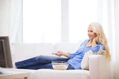 Young girl with popcorn watching movie at home Royalty Free Stock Images