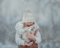 Young girl portrait with kitten under snow