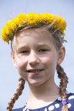 Young girl portrait in yellow dandelion garland. On blue sky background Royalty Free Stock Photography