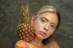 Young girl poses with pineapple fruit on shoulder stock photo