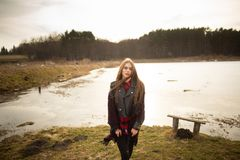 A young girl poses on the shore of a lake, throwing a scarf on her royalty free stock photos
