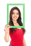 Young girl posing behind a picture frame Stock Images