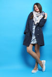 Young girl. Posing in a blue coat on a blue background Stock Images