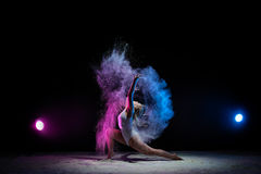Young girl posing in color dust cloud in studio Royalty Free Stock Image