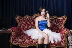Young girl posing on a couch. In studio with white net skirt and telephone Stock Photos