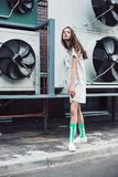Young girl posing in green socks and white dress on the street. Streetstyle, fashion. Young girl posing in green socks and white dress on the street. Propellers Royalty Free Stock Image