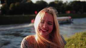 Young girl posing on the gren grass near the river at sunset close up look at camera nd laughs stock video
