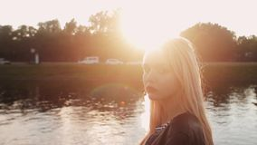 Young girl posing on the gren grass near the river at sunset stock video