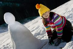 Young girl posing with her snowman Royalty Free Stock Photo