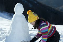 Young girl posing with her snowman Royalty Free Stock Photography
