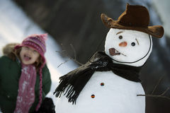 Young girl posing with her snowman Royalty Free Stock Image