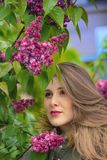 Young girl posing near lilac bushes royalty free stock photography