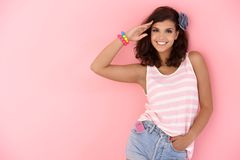 Young girl posing over pink wall smiling Stock Photo