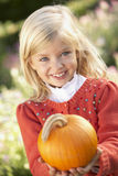Young girl posing with pumpkin in garden. Smiling royalty free stock photo