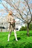 Young girl posing in the sakura garden Stock Photo