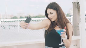 Young girl posing for selfie with goblet of blue cocktail on the beach stock footage