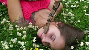 Young girl posing with a snake around his neck on the nature stock video footage