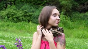 Young girl posing with a snake around his neck on the nature stock footage
