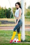 Young girl posing with a soccer ball at football goal stock image