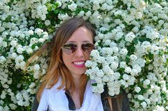 Young girl posing surrounded by flowers. Happy young girl wearing sunglasses posing surrounded by flowers Stock Photos