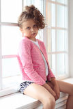 Female child. Young girl is posing by the window Royalty Free Stock Photography