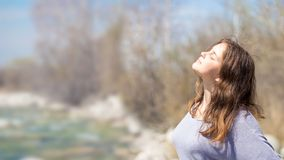 Young girl with positive emotions. Relaxed, pleased with a smile on her face. Spring natural background, forest and river. Young girl with positive emotions stock image