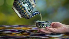 Young girl pouring tea into piala in asian cafe, Samarkand, Uzbekistan