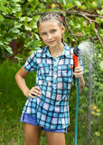 Young girl pours water from hose Stock Photos