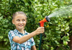 Young girl pours water from hose Royalty Free Stock Image