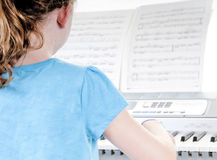 Young girl practicing piano Stock Photos
